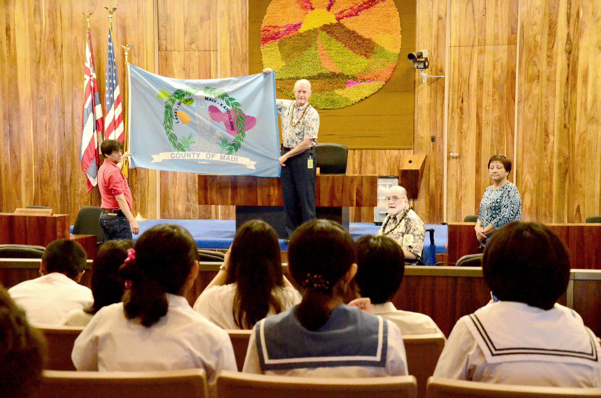 Mike White holding Maui County flag